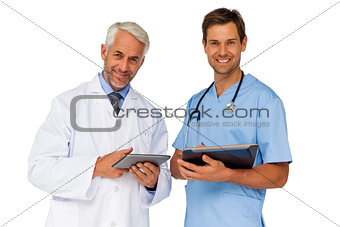 Portrait of male doctor and surgeon with digital tablets