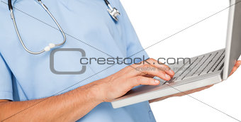 Close-up mid section of a male surgeon using laptop