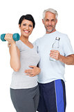 Happy fit couple with dumbbell and water bottle