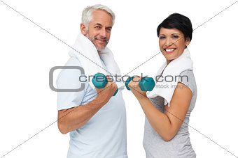 Fit mature couple exercising with dumbbells