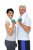 Portrait of a fit mature couple exercising with dumbbells