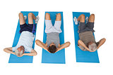 Full length of three men doing abdominal crunches