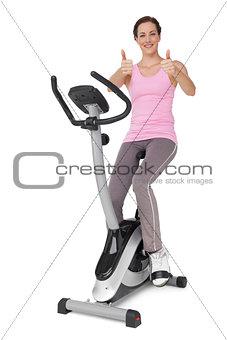 Beautiful woman gesturing thumbs up on stationary bike