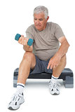 Full length of a senior man exercising with dumbbell