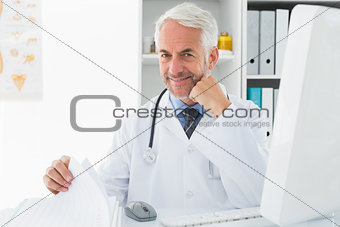 Mature male doctor with computer at medical office