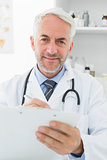 Smiling male doctor writing reports in medical office