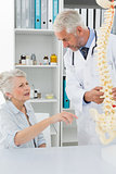 Male doctor explaining the spine to senior patient