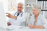 Doctor with female patient reading reports on computer