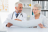 Doctor with patient reading reports at medical office