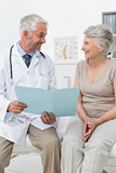 Male doctor and senior patient with reports