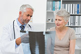 Male doctor explaining x-ray to senior patient