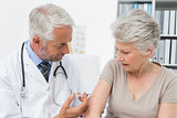 Male doctor injecting senior female patient