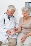 Male doctor taking a senior females pulse