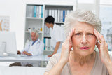 Senior patient suffering from headache with doctors at medical office