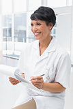 Smiling female doctor writing on clipboard