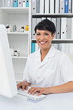 Confident smiling female doctor using computer