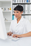 Concentrated female doctor using computer