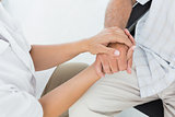 Mid section of a doctor holding patients hand