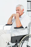 Side view of a sad senior man sitting in wheelchair