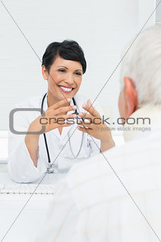 Young female doctor attentively listening to senior patient