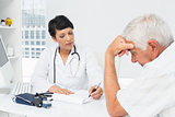 Doctor explaining reports to worried senior patient
