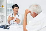 Female doctor explaining reports to senior patient