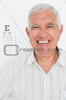 Portrait of smiling senior man with eye chart in background