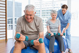 Female therapist assisting senior couple with dumbbells