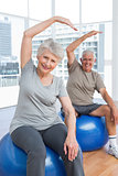 Senior couple doing stretching exercises on fitness balls