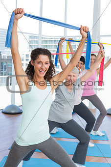 Class holding up exercise belts at yoga class