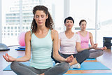 Women in lotus pose with eyes closed at fitness studio