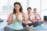Women with eyes closed and joined hands at fitness studio