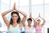 Sporty women with joined hands over head at fitness studio