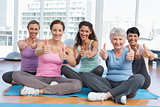 Women gesturing thumbs up in yoga class
