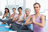 Class sitting with joined hands in a row at yoga class