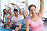 Trainer with women in row stretching hands at yoga class