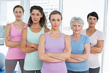 Confident women with arms crossed in yoga class