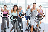 People working out at spinning class while gesturing thumbs up