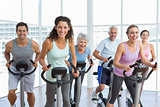 Happy people working out at spinning class