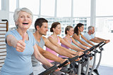 Woman gesturing thumbs up with class at spinning class