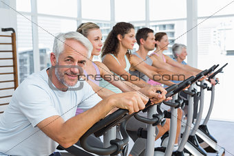 People working out at spinning class in gym
