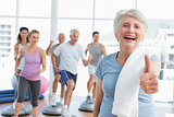 Senior woman gesturing thumbs up with people exercising