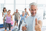 Senior man gesturing thumbs up with people exercising in fitness studio