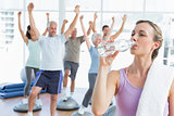 Woman drinking water with people stretching hands at fitness studio