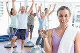 Woman holding bottle with people stretching hands at fitness studio