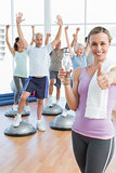 woman gesturing thumbs up with people stretching hands fitness studio