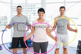 Fitness class holding hula hoops in gym