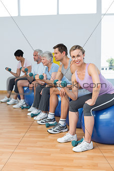 Class with dumbbells sitting on exercise balls in gym