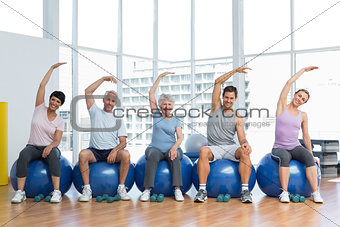 Class sitting on exercise balls and stretching hands in gym