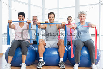 Class holding exercise belts while sitting on fitness balls